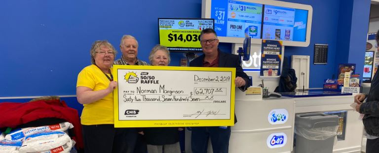 December winner Norman Marginson and family with Corey Taylor, Senior Manager, CNIB